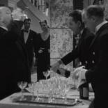 1:00 En la gran fiesta en la mansión de Claude Rains, bebiendo champán y yéndose rápidamente.