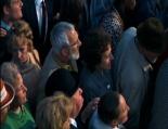 0:03:52 En el centro de la multitud con sombrero.