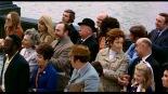 0:03:09 En el centro de la multitud con sombrero.
