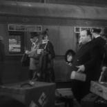 1:30 En la Estación Victoria de Londres, fumando un cigarro y con un abrigo negro.